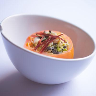 Presentación de tomate relleno de ensalada de pato
