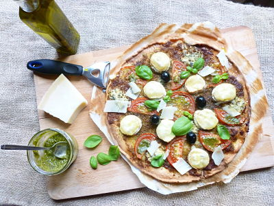 Pizza con pesto de nueces, tomates y quesos